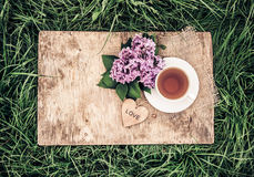 A cup of black tea and flowers of fragrant lilacs on an old wooden board. Tea in the garden. Vintage tinting Royalty Free Stock Photos