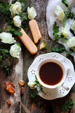 Cup of black tea and flowers of wild rose Royalty Free Stock Photos