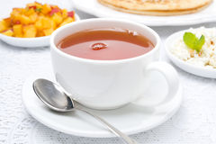 Cup of black tea and fresh breakfast in the background Royalty Free Stock Photography