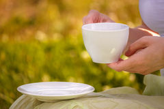 Cup of black tea in the hands of a young girl on picnic Stock Photos