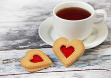 Cup of black tea and heart shaped cookies Stock Photos