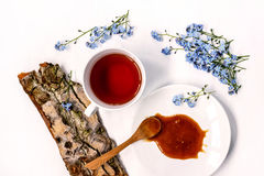 Cup of black tea with honey on herbs, forget-me-nots and tree bark on a white background Stock Images