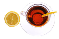 A cup of black tea with lemon. Transparent cup with black tea and a lemon isolated Stock Image
