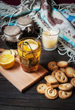 Cup black tea with lemon, ginger and cookies on dark wood.  Stock Photography