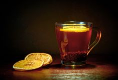 A cup of black tea and lemon, pieces of dried orange. Dark background, warm shades, steam royalty free stock photos