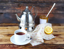 Cup of black tea with a lemon, teapot and jam. On the wooden background Royalty Free Stock Images