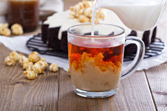 Cup of black tea with milk. Pouring over stock image