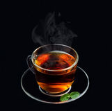 Cup of black tea with mint and smoke on a black background Stock Photos