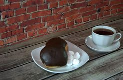 A cup of black tea on a saucer and a plate with two donuts in chocolate icing and pieces of bize, lie on a wooden table against a royalty free stock image