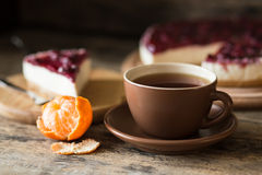 Cup of black tea with slice of cheesecake. And some mandarins on wooden background Royalty Free Stock Photo