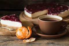 Cup of black tea with slice of cheesecake. And some mandarins on wooden background Royalty Free Stock Images