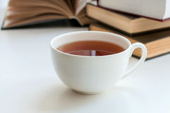 Cup of black tea and some books. To read lying on the white table stock images