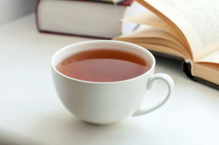 Cup of black tea and some books. To read lying on the white table stock image