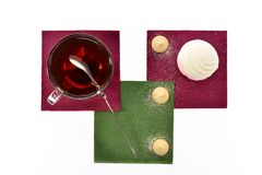 Cup of black tea with a spoonful marshmallows and cookies on colored paper napkins Royalty Free Stock Photos