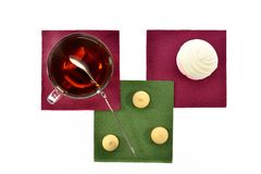 Cup of black tea with a spoonful marshmallows and cookies on colored paper napkins Stock Image