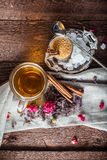 Cup of black tea with sugar cane, roses, tea leaves on a brown wooden background Stock Photo