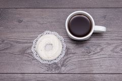 Cup of black tea with tasty delicious merengue on the brown wooden table. Top view Royalty Free Stock Photo