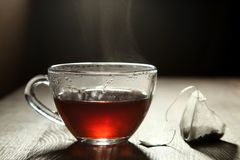Black tea and a tea bag. A cup of black tea and a tea bag on a wooden table in the dark stock photography