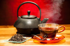 A cup of black tea with teapot in the background Stock Photography