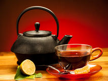 A cup of black tea with teapot in the background Royalty Free Stock Images