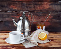 Cup of black tea in a teapot with a lemon and jam on a dark wood Stock Image