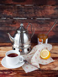 Cup of black tea in a teapot with a lemon and jam on a dark wood. Black tea in a teapot with a lemon and jam on wooden background in rustic style Stock Image
