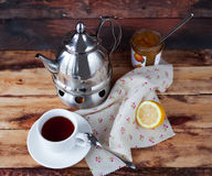 Cup of black tea in a teapot with a lemon and jam on a dark wood. Black tea in a teapot with a lemon and jam on wooden background in rustic style Stock Images