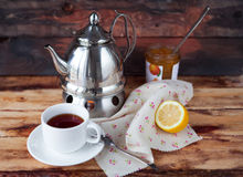 Cup of black tea in a teapot with a lemon and jam on a dark wood. Black tea in a teapot with a lemon and jam on wooden background in rustic style Royalty Free Stock Photography