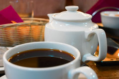 Cup of black tea and teapot on table closeup view Royalty Free Stock Image