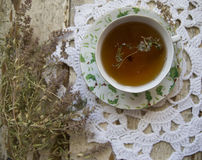 Cup of black tea with thyme & crochet doily on a retro background. Still Life with a cup of black tea with thyme and dried thyme on a white knitted lacy napkin Stock Photography