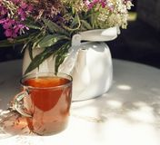cup black tea white kettle table sunlight bouquet flowers outdoor garden day summer sunlight stock image