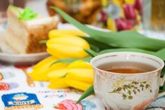 Cup of black tea, yellow tulips, tasty biscuit cake, breakfast for lovely. Wife, girlfriend, mother stock image