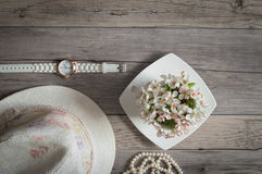 Cup of blooming flowers pear tree, beads from pearls, white clock. Royalty Free Stock Photos