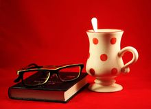 Cup, book and sunglasses. Cup with red polka dots, a book and reading glasses stock photo