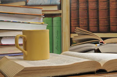 Cup and books. Large yellow cup of tea among the stack of books Stock Images