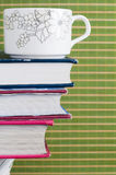 Cup books. Cup on books, green background Royalty Free Stock Photo