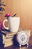 Cup, books and flowers on wooden background Stock Photos