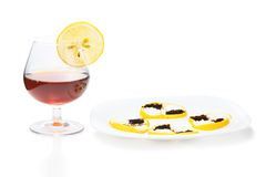 Cup of brandy  with lemon snack Royalty Free Stock Image