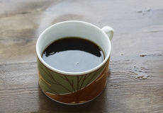 A cup of brew on a wooden table Royalty Free Stock Image
