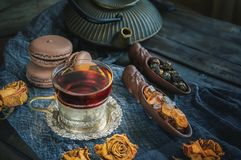 A Cup of brewed black tea. Two ceramic spatulas with caramel sugar and Rolled leaves in a large pearl. Chinese tea from. Yunnan. Bi Lo Chun. Copy spase stock image