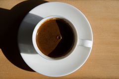 Cup of brewed coffee in a saucer. On a wooden table in the room Royalty Free Stock Image