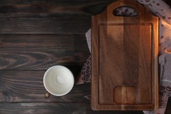 Cup with brown wooden cutting board. On a brown table top Stock Photo