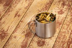 Cup of bullets on a table. A tin coffee cup with 556 nato green tip bullets in it placed on a wooden table stock photos
