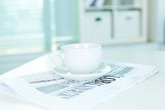 Cup and business newspaper Stock Photos