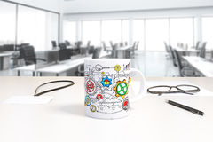 Cup with business scheme print and badge on the table in open sp Stock Photo