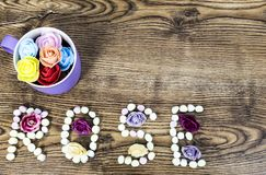 Cup of button roses with the text rose formed with marshmallows on wooden table. royalty free stock photos