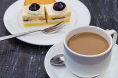 A cup of cafe latte and cake Stock Images