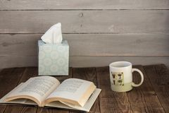 A cup with cafe an open book and a box with napkins stock photography