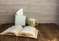 A cup with cafe an open book and a box with napkins stock images