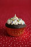 Cup cake. In a silver paper on a red background royalty free stock photo